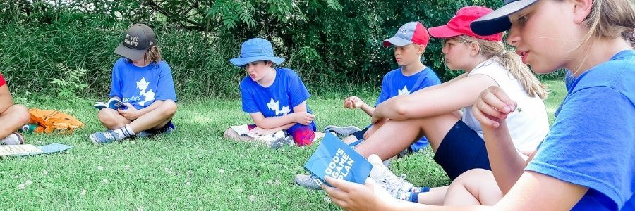 Children at camp reading Bible during Bible time